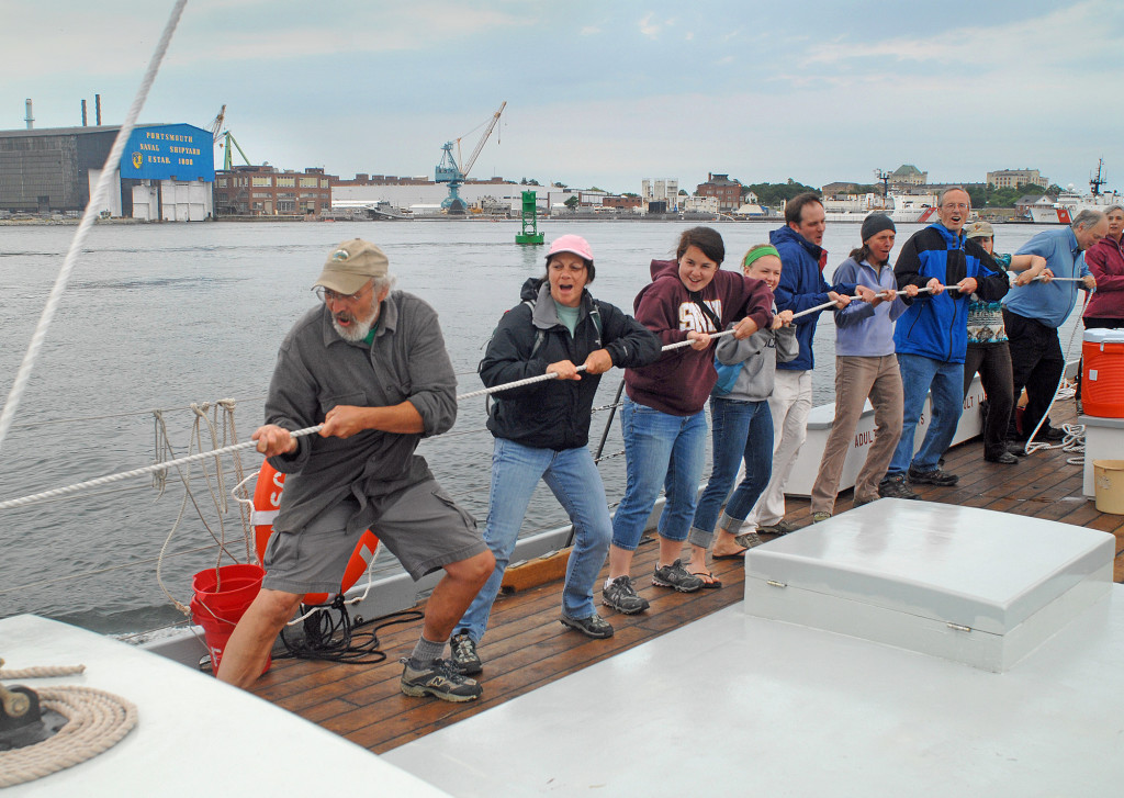 """During an evening cruise, a crew of teachers haul on the main sheet to set the sail on the gundalow """"Piscataqua"""" on the Piscataqua River in Portsmouth, NH. The Gundalow Company, Portsmouth, NH. Photograph by Ralph Morang"""