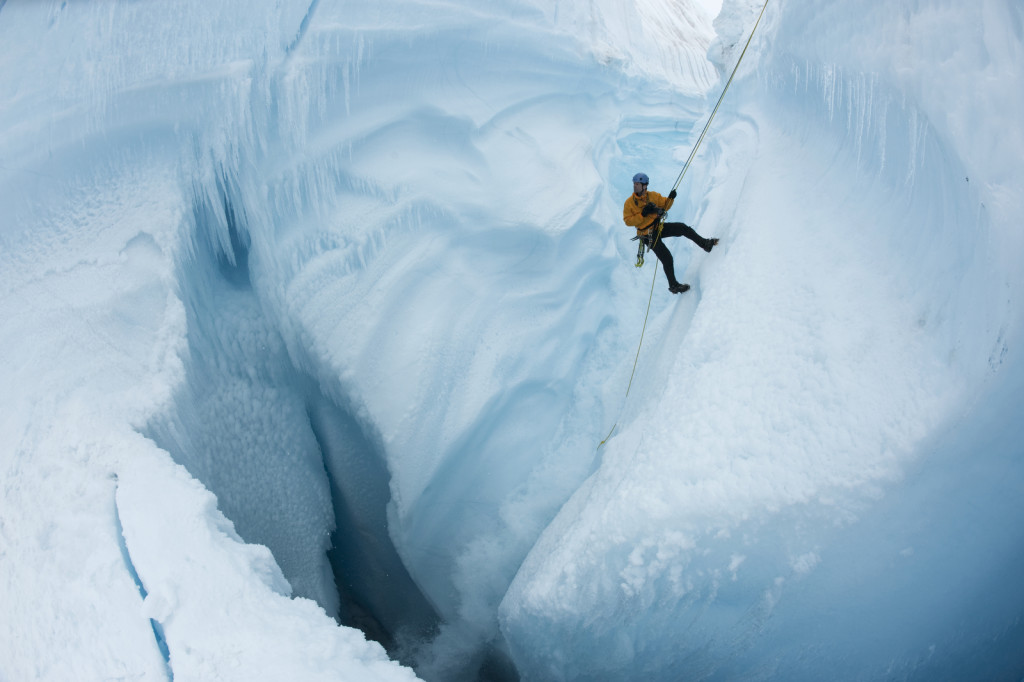 Rappeling into Survey Canyon, looking down at moulin channel dropping meltwater 2000 vertical feet into crevasses through Greenland Ice Sheet. EIS director, James Balog, is shown.