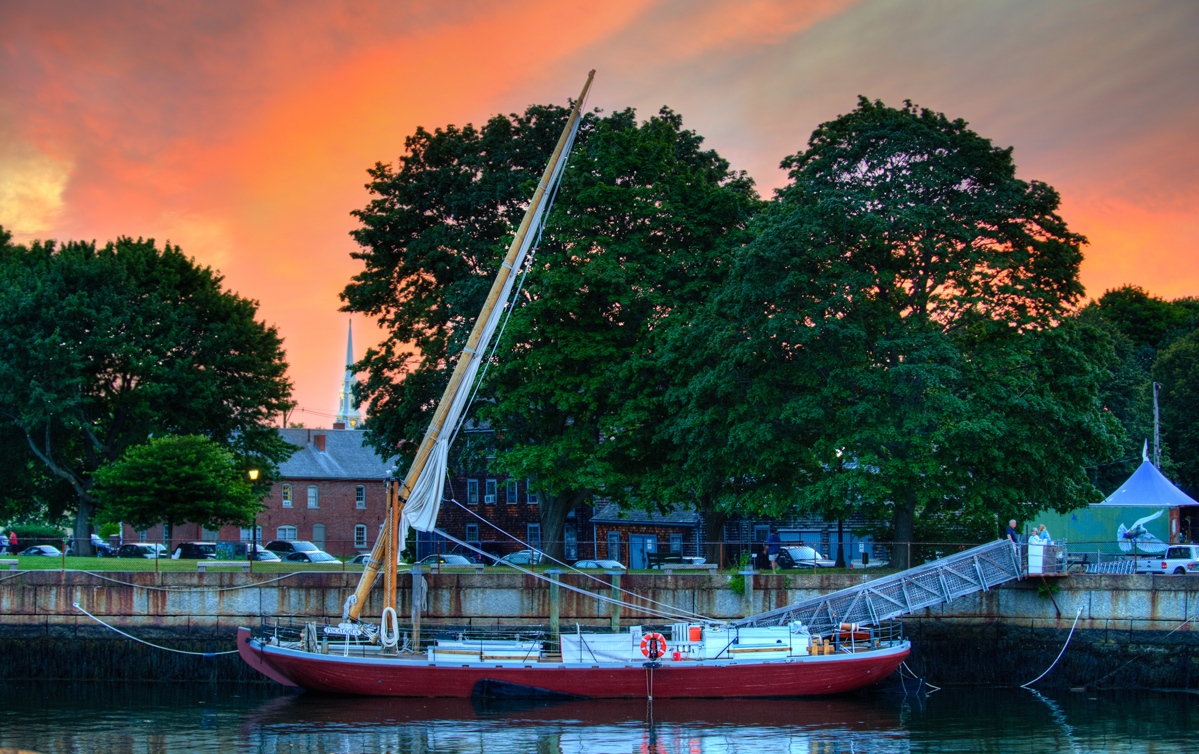 The gundalow Piscataqua sits docked in front of Prescott Park in Portsmouth NH at sunset. The steeple of the North Church is illuminated in the background by lights that have just come on.